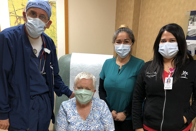 Catinean surrounded by her LLU cancer care team