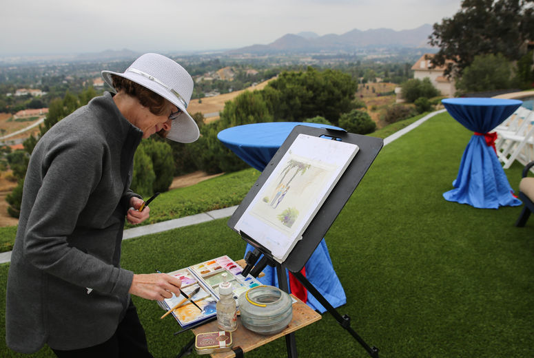 female painter paints the hillside with watercolor