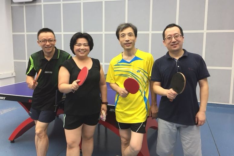 four people holding ping pong paddle